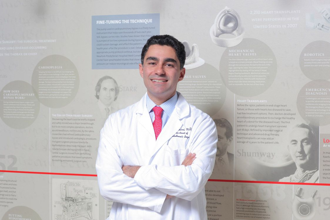 Surgeon standing in front of wallpaper with various techniques.