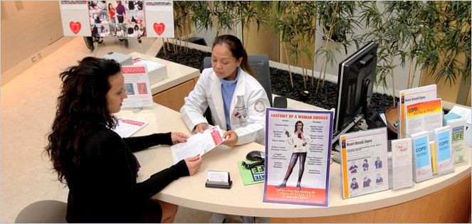 Physician hands a patient an educational brochure at the help desk.