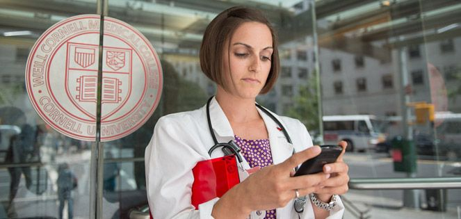 Resident checks her phone in front of Weill Cornell Medicine doors.